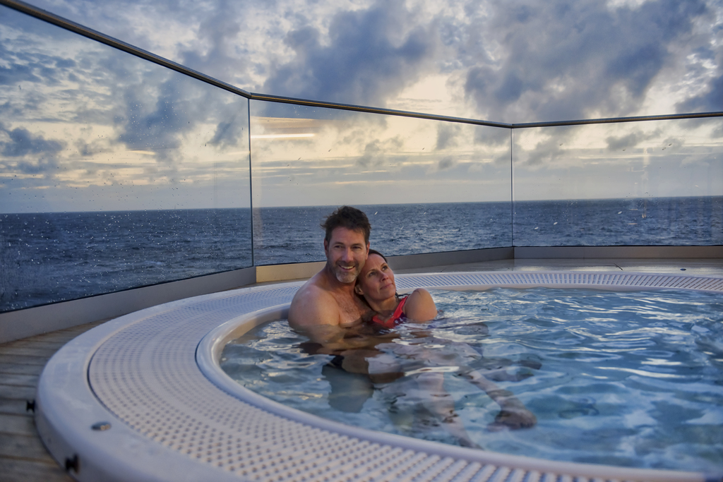 A couple using a hot tub at sunset