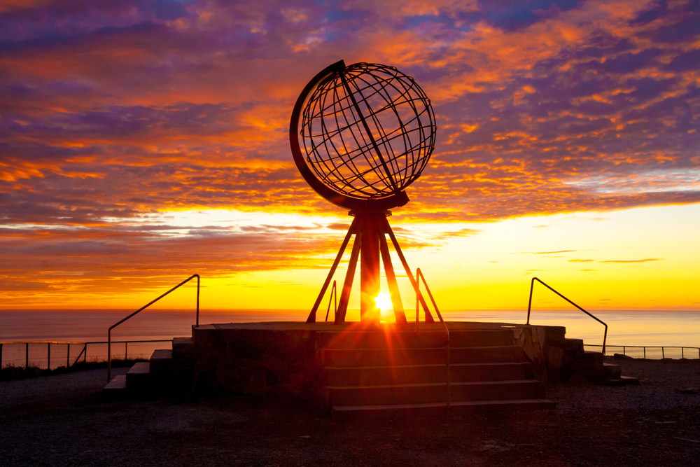 The midnight sun shining through a globe sculpture