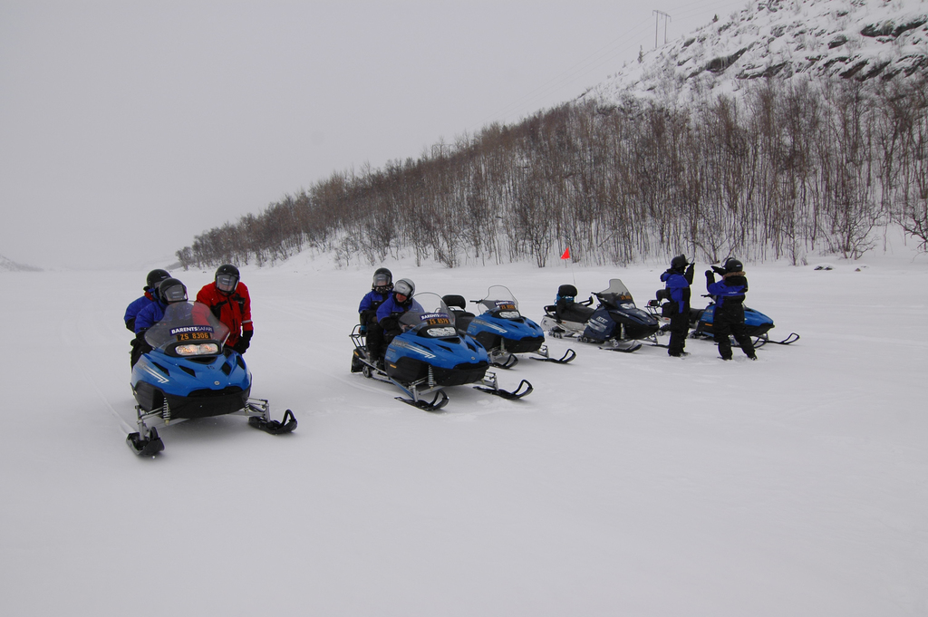 People in the snow on snowmobiles